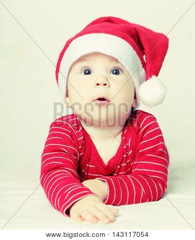 Happy New Year surprised baby in Santa hat Christmas concept
