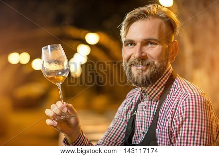 Close-up portrait of a handsome bearded blond sommelier in apron and checkered shirt with wine glass in the old cellar.