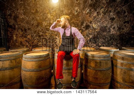 Portrait of a handsome sommelier in apron and checkered shirt sitting on the barrel in the old cellar.