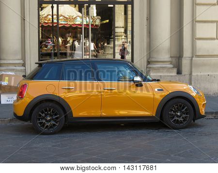FLORENCE ITALY - CIRCA JULY 2016: yellow orange Mini Cooper car parked on a street of the city centre