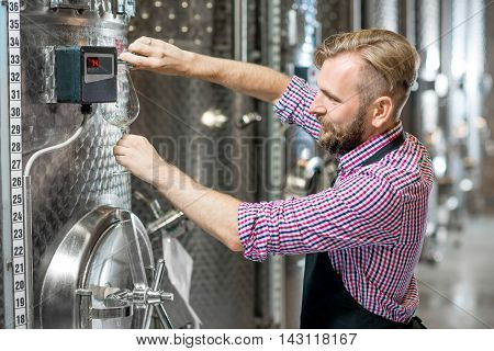 Handsome wine maker in working apron pouring wine to the glass at the wine manufacture with metal tanks for wine fermentation. Wine production at the modern factory