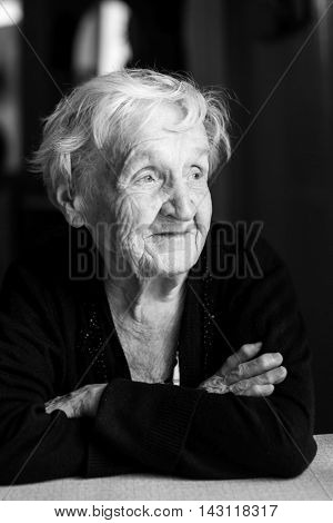 Elderly woman close-up black and white portrait.