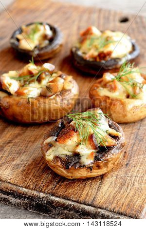 Baked stuffed mushroom caps with cheese, meat and spices. Mushrooms stuffed on a wooden background. Delicious simple appetizer recipe