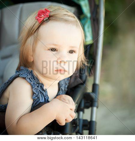 beautiful Child in pram outdoors on gray