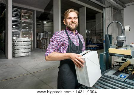 Handsome packer in working apron with box on the packaging line at the manufacture.