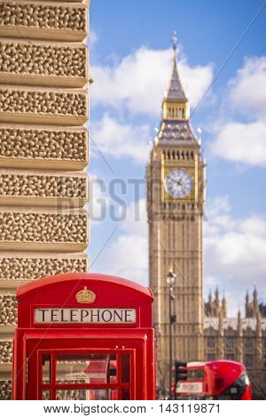 Traditional red british telephone box with iconic double decker bus and Big Ben at the background - London, UK