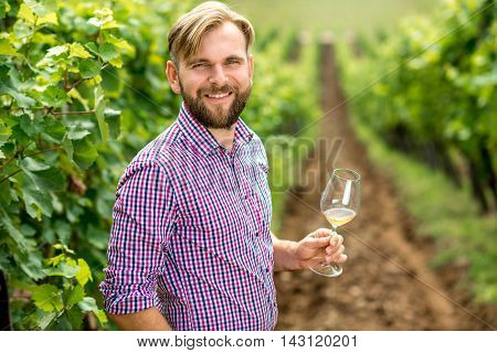 Portrait of vinery owner with wine glass on the vineyard