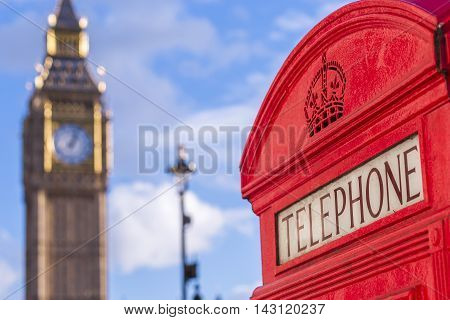 The Big Ben with iconic red British telephone box on a sunny afternoon with blue sky and clouds - London, UK