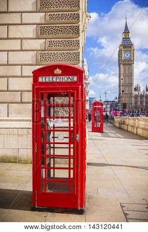 Iconic Red British telephone box with Big Ben on a sunny afternoon with blue sky - London UK