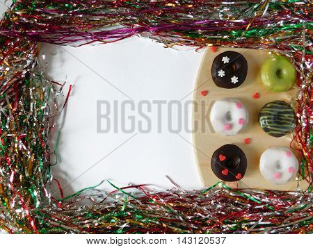 Donuts on a cutting board surrounded by christmas decoration