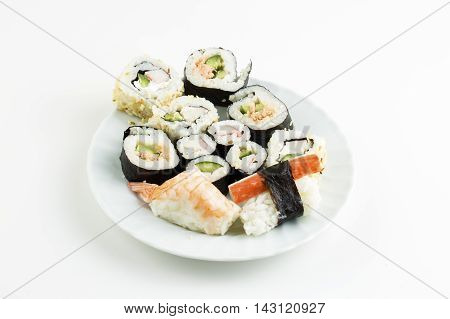 Plate of sushi, with soy sauce and chopsticks, over bamboo background