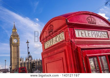 London, UK - Traditional British red telephone box with Big Ben on a sunny day with blue sky