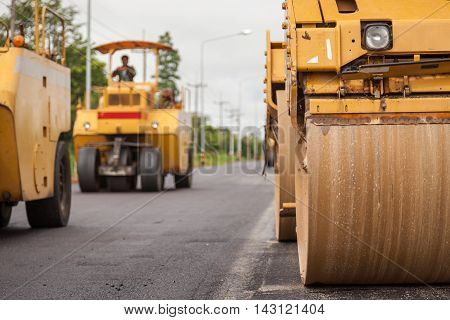 Road construction works with roller compactor machine and asphalt finishers