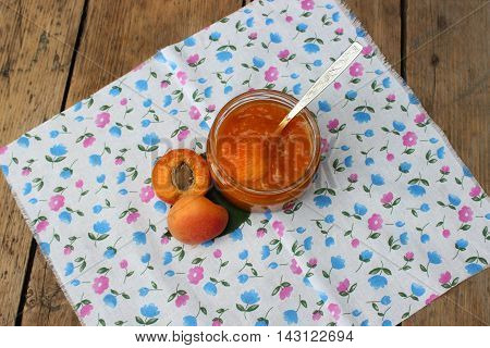 Ripe apricots and jar of jam are on colored napkin