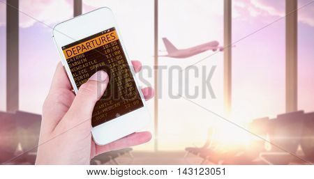 Hand showing smartphone against airplane flying past departures lounge window