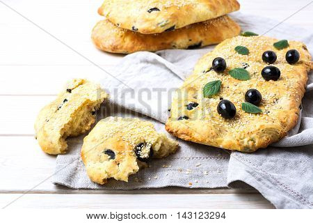 Fresh Italian bread with olive garlic and herbs. Homemade traditional Italian bread focaccia on the linen napkin.