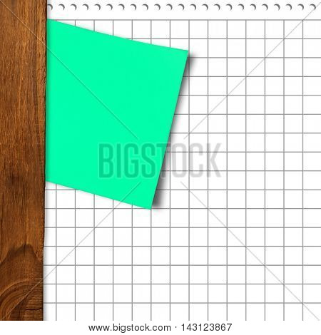 Green adhesive note against spiral notepad