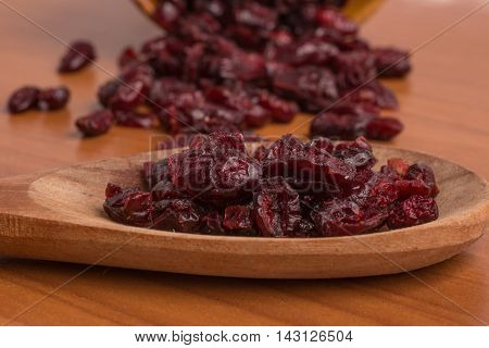 Dried Cranberries into a spoon over a wooden table