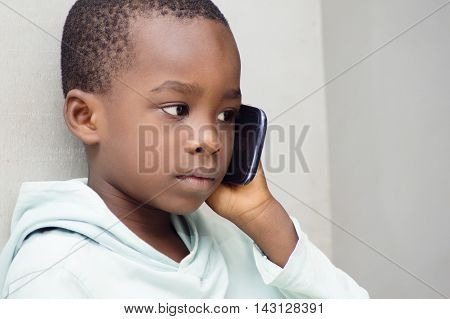 Child listening with great attention that his mother told him on the phone