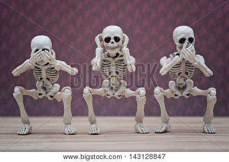 Three skeletons pose as three wise monkey