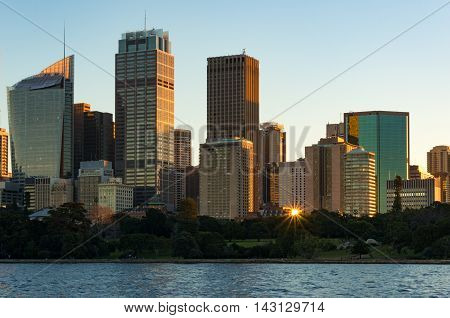 Sydney CBD skyscrapers on sunset with sun reflecting from windows. Modern urban cityscape with office buildings