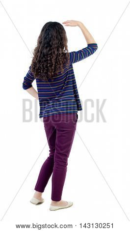 back view of standing young beautiful  woman.  girl  watching. Rear view people collection.  backside view of person. Long-haired curly girl in a blue jacket stares into the distance somewhere.