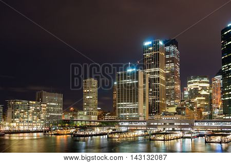 Circular Quay railway train station and ferry wharfs with Sydney Central Business District cityscape skyscrapers at the background. Night shot long exposure copy space