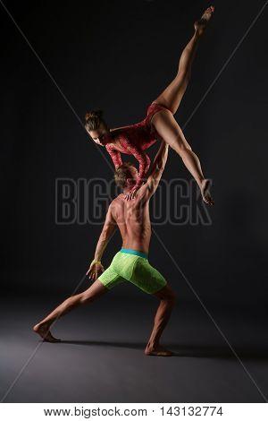 Acrobatics. Duet of gymnasts perform trick in studio