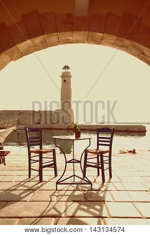 Old vintage cafe and lighthouse on the sea Rethymnon Crete impressions of Greece