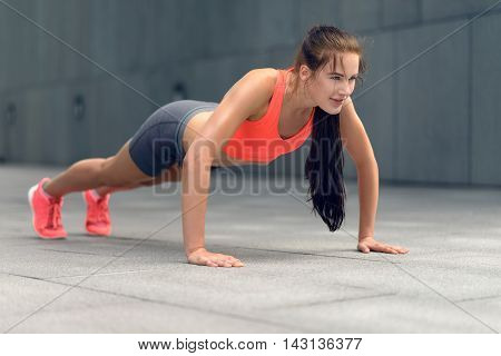 Fit Young Woman Doing Push-ups In Town