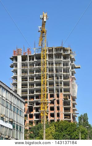 Building site with high-rise block under construction in an urban environment dominated by a large industrial crane