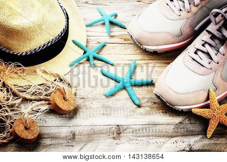 Summer holiday setting with straw hat and seashells. Copy space