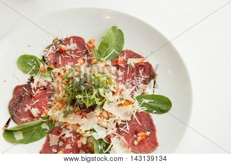 Carpaccio made from slice beet sirloin decorated with cheese