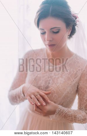 Charming delicate bride dressing engagement ring in preparations for wedding.