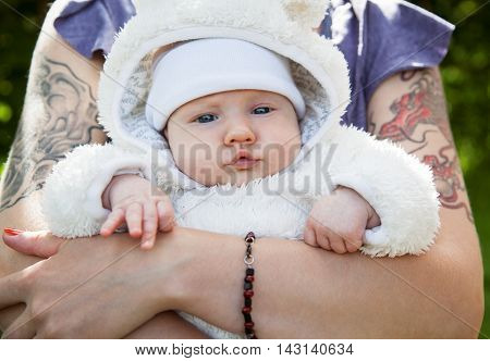 Mother holding in the hands a little cute baby in a white fuzzy overalls
