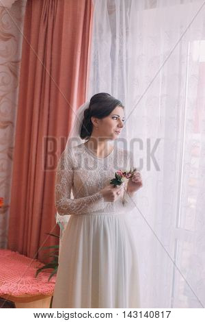 Half-length portrait of charming bride in wedding dress near window holding boutonniere.