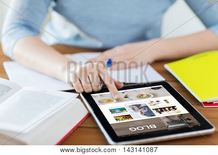 technology, media, internet and people concept - close up of student woman with blog web page on tablet pc computer screen and notebook at home