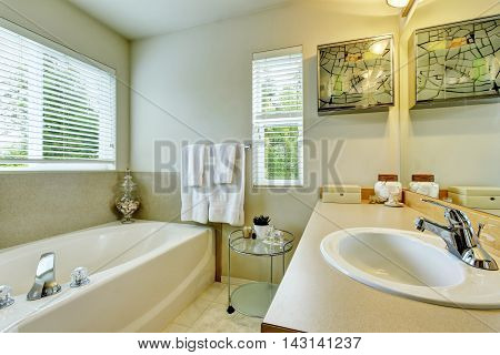 Bathroom Interior With White Bath Tub, Vanity Cabinet And Tile Floor.