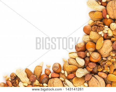 Background of mixed nuts - hazelnuts, almonds, walnuts, pistachios, peanuts, pine nuts peeled and not peeled - with copy space. Isolated one edge. Top view or flat lay