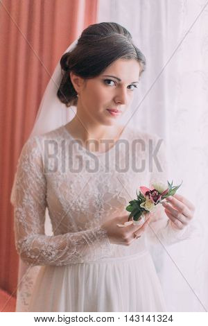 Half-length portrait of beautiful bride in wedding dress near window holding cute floral boutonniere.