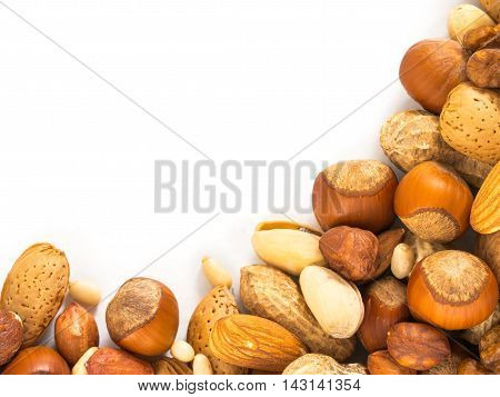 Background of closeup mixed nuts - hazelnuts, almonds, walnuts, pistachios, peanuts, pine nuts peeled and not peeled - with copy space. Isolated one edge. Top view or flat lay
