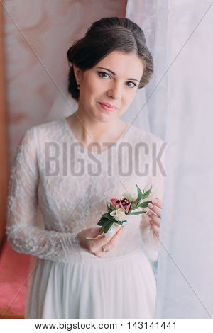 Half-length portrait of beautiful bride in wedding dress near bright window indoor holding boutonniere.
