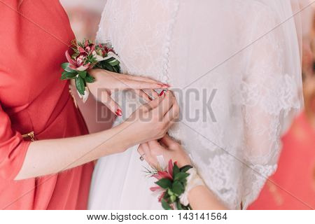 Bridesmaid help to fix gowmn buttons on bride's back.