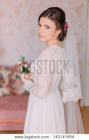 Half-length portrait of beautiful sensual young bride in wedding dress looking over her shoulder indoors holding boutonniere.