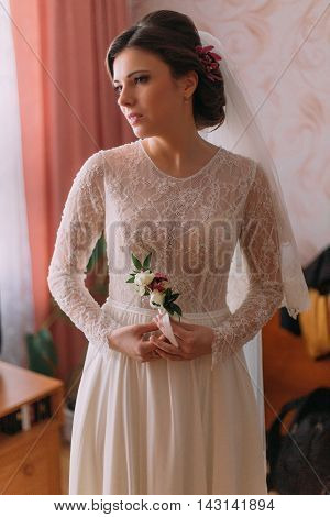 Half-length portrait of beautiful bride in wedding dress posing indoors holding little floral boutonniere.