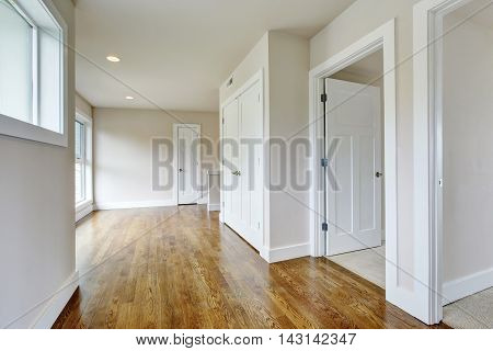 Empty Hallway Interior In White Tones With Hardwood Floor