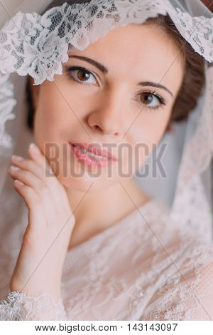 Close-up portrait of beautiful sensual bride in wedding gown with lifted veil posing indoors in dressing room before the ceremony.