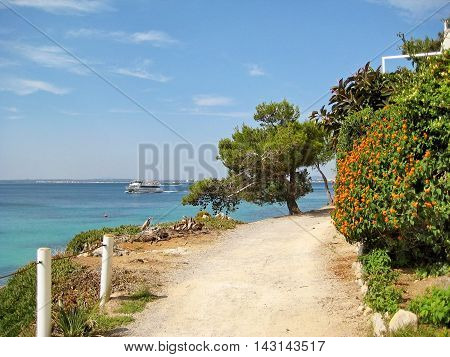 Alcudia Majorca Spain - June 26 2008: Path / road at coast outside of Alcudia - bushes and tree near turqoise mediterranean sea with ship