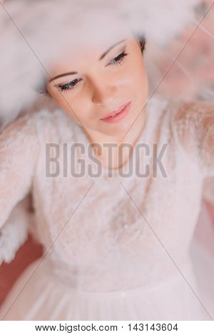 Close-up portrait of beautiful sensual bride in wedding dress lifting her veil.