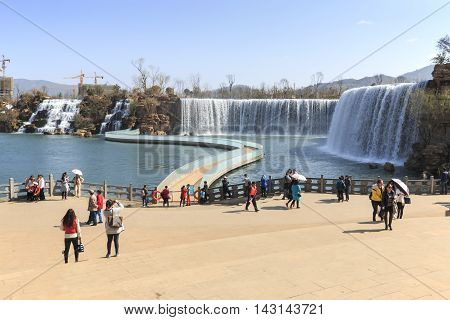 Kunming, China - March 4, 2016: Tourists Wisiting The Kunming Waterfall Park Featuring A 400 Meter W